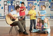 Homme joue de la guitare avec enfants
