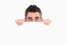 Homme se cache panneau blanc