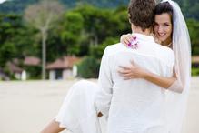 Marié porte sa femme sur la plage