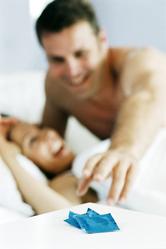 Couple au lit prenant un préservatif