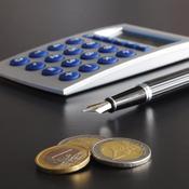 Calculatrice, stylo et pièces sur un bureau