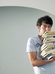 Homme tient pile de livres