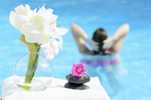 Femme piscine fleurs serviette et galets