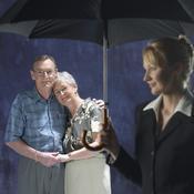 Couple au second plan, jeune femme sous parapluie au premier plan