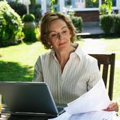 Femme seule avec pc et papiers dans son jardin