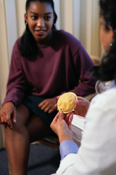 Gynéco présentant un diaphragme à une patiente