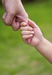 Main d'enfant tient le doigt d'un adulte sur fond vert