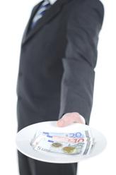 Homme en costume tend une assiette avec billets