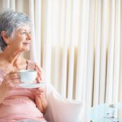 Femme d'âge mûr seule regarde par la fenêtre