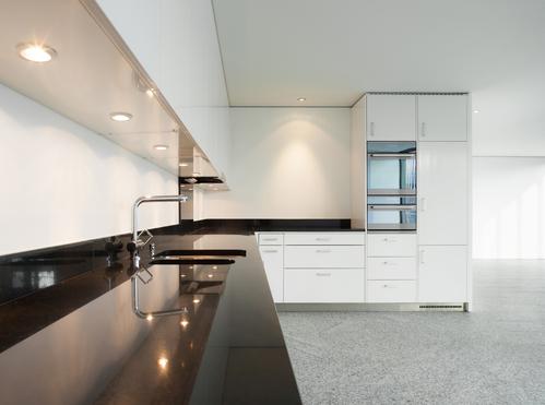 Intérieur de cuisine avec plan de travail noir éclairé par des spots luminaires cuisine
