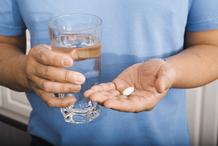Homme verre d'eau cachets main