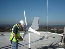 Intervention d'un professionnel sur une éolienne sur le toit d'un immeuble