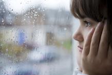Petite fille regard vide fenetre pluie