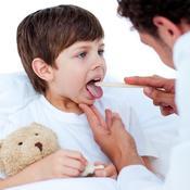 Enfant avec son doudou osculté par médecin