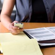 Femme avec téléphone dans la main, papier et agenda