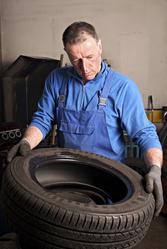 Mecano regarde pneu