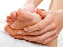 Une femme se fait un massage du pied
