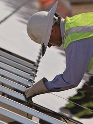 Ouvrier installe un panneau photovoltaïque sur un toit