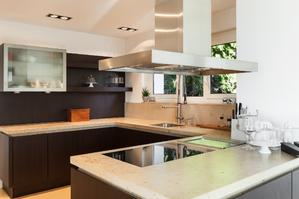 Intérieur de csuisine ouverte avec plan de travail en marbre et en U (en angle).  Présence de meubles en bois et d'une hotte d'aspiration.