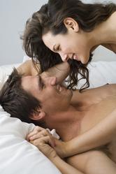 Couple heureux sourires lit