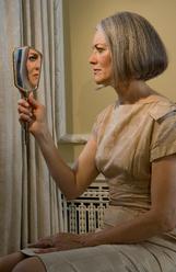 Femme mure regarde dans un miroir