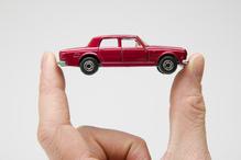Deux doigts tenant une voiture miniature