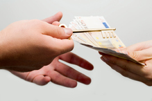 Deux mains s'échangent des clés contre des billets