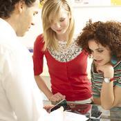 Jeunes filles et vendeur autour de portables