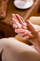 Femme agée se touche les mains