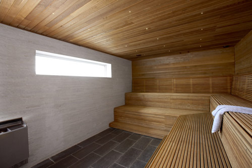 Sauna de grande taille en bois avec une petite vitre en hauteur et un poêle électrique