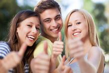 Groupe jeunes souriants pouces