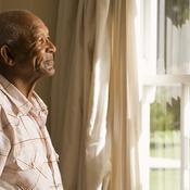 Homme seul regarde par la fenêtre