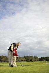 Grand-père joue au golf avec petit-fils