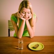 Femme regarde tranche de pain et verre d'eau