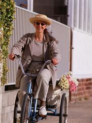 Femme velo trois roues fleurs rue sourire