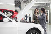 Femme mecano et cliente moteur avant ouvert garage