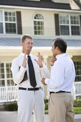 2 hommes discutent ensemble devant maison